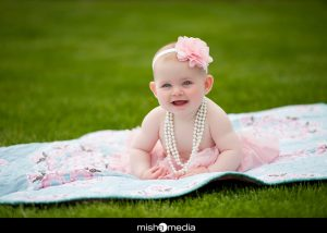baby with pearl necklace on the blanket on the grass