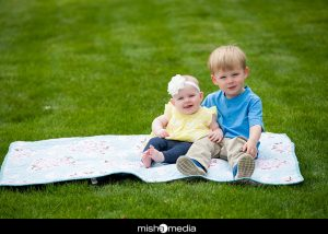 baby and brother on blanket on the grass